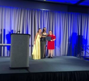Margaret Lee accept the Charter of the Year Award award from International President Tana Early and International Trustee Maria Landron.